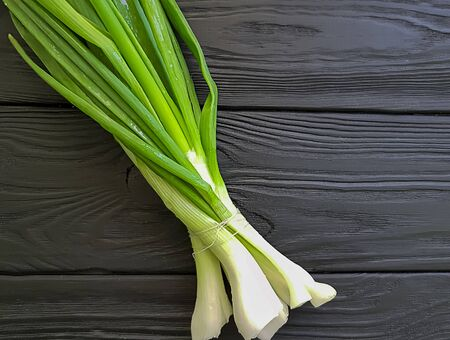 green onions on wooden background natural