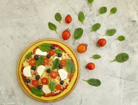 pizza, olives, tomatoes on a concrete background