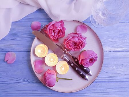 plate, candle flower rose on wooden background