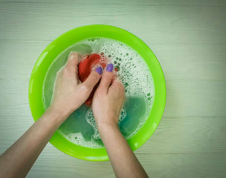 female hands wash clothes in a basin Stock Photo