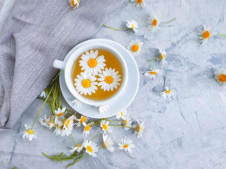 chamomile flower tea on concrete background