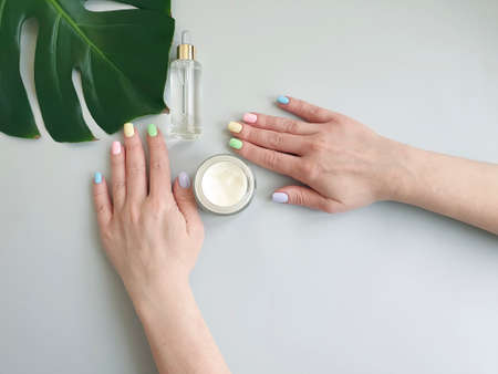 female hands beautiful manicure monstera leaf on a colored background cream