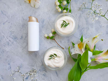 cosmetic cream, flower on on a concrete background 写真素材