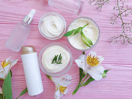 cosmetic cream, flower on on a wooden background