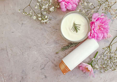 cosmetic cream, flower on on a concrete background Imagens