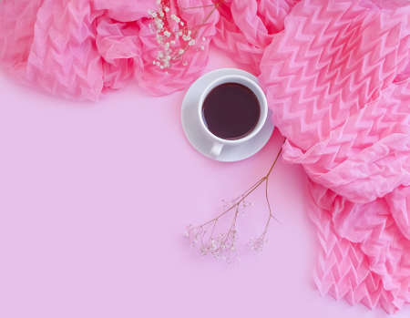 cup of coffee, a scarf on a colored background, gypsophila flower, morning