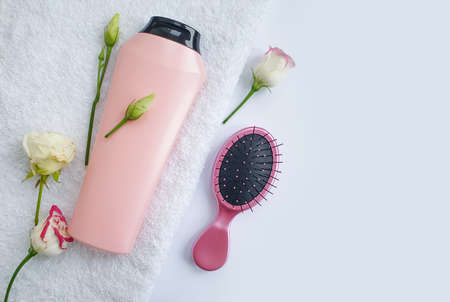comb, shampoo rose flower on a light background