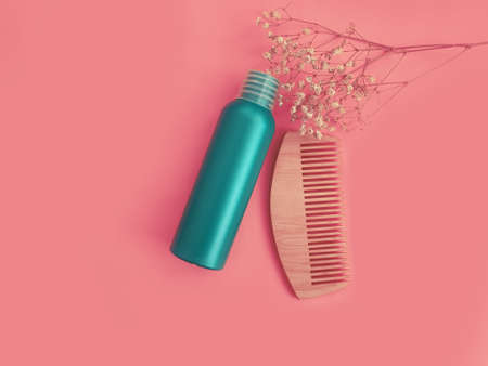 shampoo, wooden comb on a colored background
