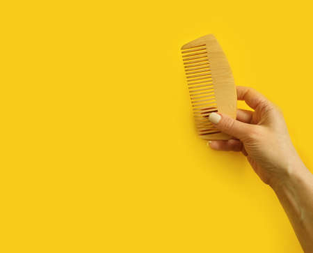 female hand holding a wooden comb on a colored background