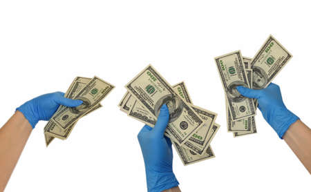 hand in a medical glove holds dollars