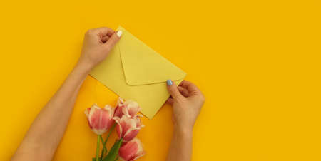 female hands hold an envelope, a bouquet of tulips