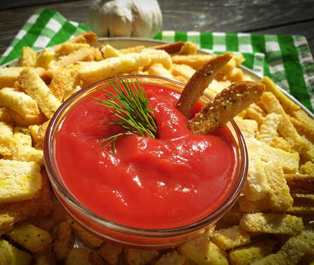 ketchup, bread croutons on a wooden background