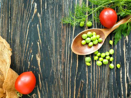 green peas, spoon, tomato on wooden background