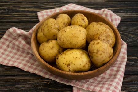 raw potatoes on wooden background Фото со стока