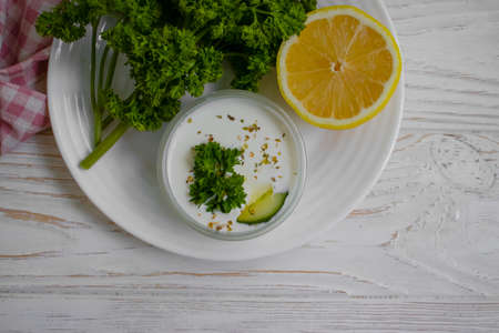 tzatziki sauce, lemon, cucumber on concrete background