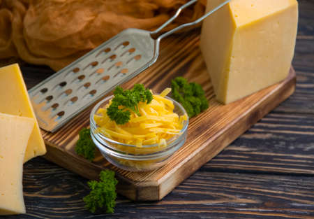 grated cheese, parsley on a wooden background