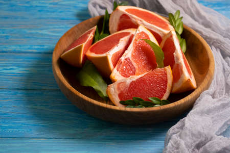 fresh grapefruit slices on wooden background