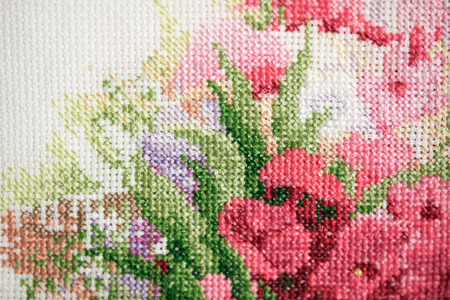 Colorful fragment of a cross-stitch embroidery with pink flowers. Archivio Fotografico - 108386709
