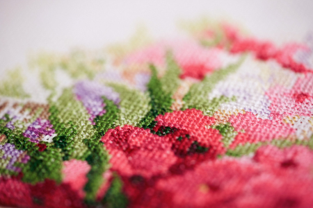Colorful fragment of a cross-stitch embroidery with pink flowers. Archivio Fotografico - 108386710
