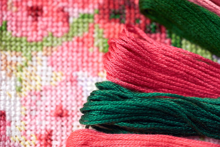 Colorful threads on a fragment of a cross-stitch embroidery. Archivio Fotografico - 108386711