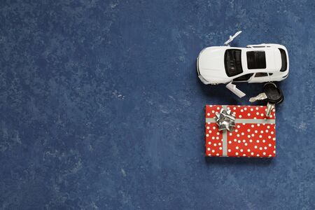 White car and car keys on a blue background. Holiday gift for daddy's day. Copy space.