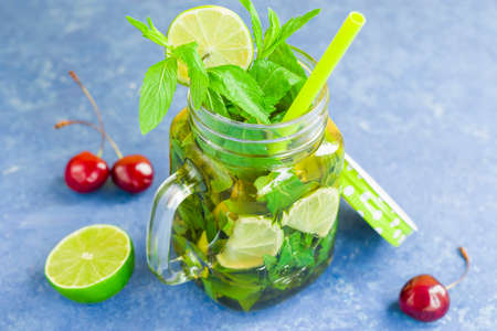 Non-alcoholic cold mojito in a glass mug with a cocktail tube. Lemonade with lime and mint on a light background. Cherry carving.