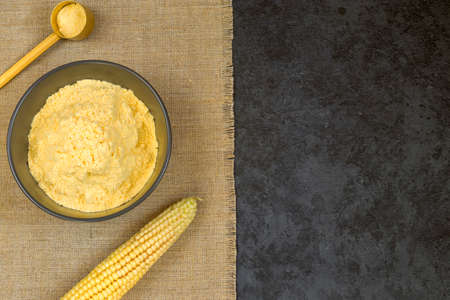 Corn grits in a bowl on dark