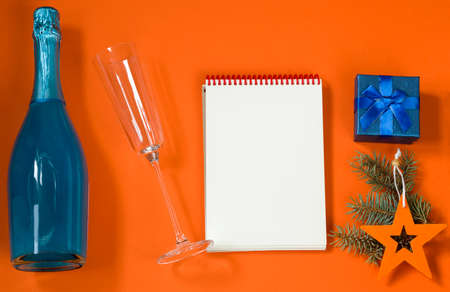 New Year concept. A notebook for writing down goals or plans for the coming year. Christmas toys, blue gift box, champagne and a glass for him on an orange background. top view, lifestyle. Copy space