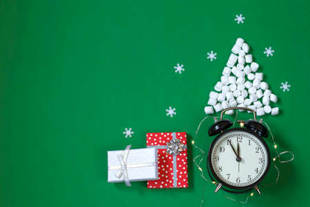 Greeting card with red and white gift boxes, Christmas tree made of marshmallows with snowflakes on a green background. Black alarm clock with a time indicator of about twelve o'clock. Copy space. Stock Photo