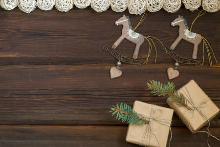 Christmas wooden toys rocking horse, gift boxes in craft paper, a garland from natural material on a dark wooden background. New Year concept. Top view. Copy space.