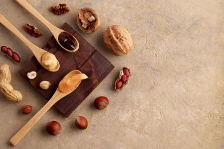 Butter, nut paste in wooden spoons with ingredients on a light background. Homemade Raw Organic Hazelnut, Peanut, Walnut. Concept for natural and vegetarian products. Top view, flatlay. Copy space