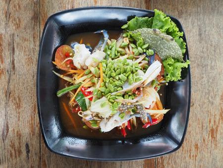 Papaya salad with Crab sauce on a wooden.