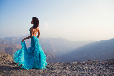 Glamorous young woman in a long light clue dress standing in the mountains with amazing view on the sunset