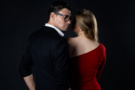 sexual intimacy: Young couple in evening gown in black background Stock Photo
