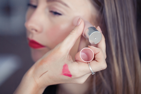 Makeup artist hand with cosmetic highlighter with model face