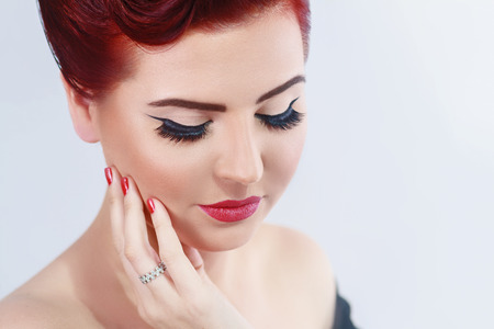 Vintage red hair model with retro hairstyle and makeup, isolated