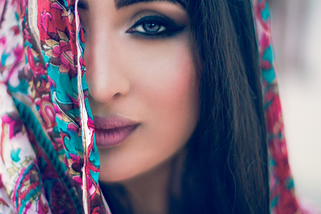 Tradition south asian woman with beautiful face looking at the camera covering her half face