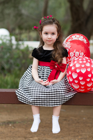 Closeup portrait of pretty serious funny girl kid sitting on the bench with red balloons
