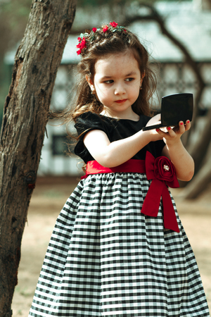 Closeup portrait of pretty serious funny girl looking at the mirror kid outdoors summer background