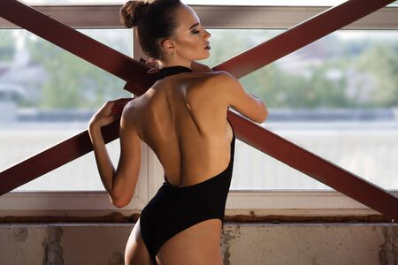 Elegant fit dancer lady standing near window with hair up showing her neck and back