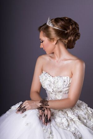 Woman model with bridal make up and hair style, wedding henna on blue background 写真素材