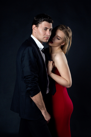 Young couple in evening gown in black background Stock Photo
