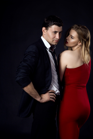 sexual intimacy: Young couple in evening gown in black background , vertical Stock Photo