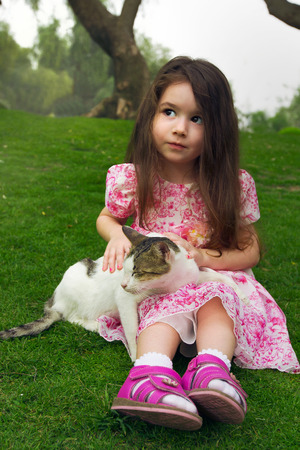 Closeup portrait of pretty serious funny girl kid holding cat  outdoors summer background Stock Photo