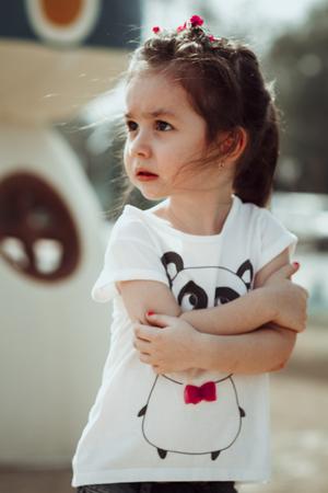 Serious litttle girl outdoor in denim scared