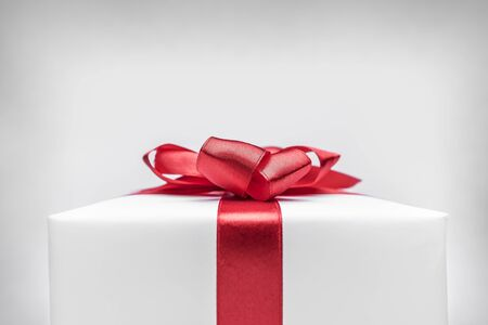 Gift box with red ribbon bow Фото со стока