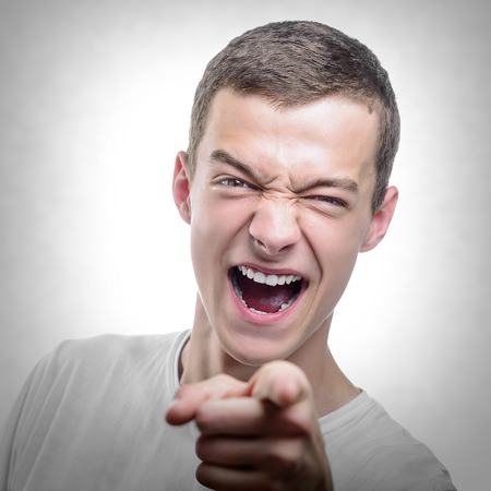 wail: Portrait of young angry man points finger. Toned photo. Stock Photo