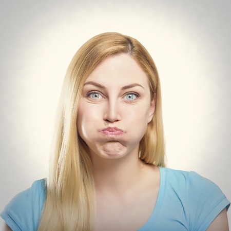 pout: Portrait of a beautiful young blonde woman making pout. Toned photo.