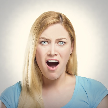 mouth opened: Shocked blonde lady with her mouth opened. Toned photo.