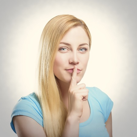 shush: Attractive blonde holding a finger to her mouth. Toned photo background.